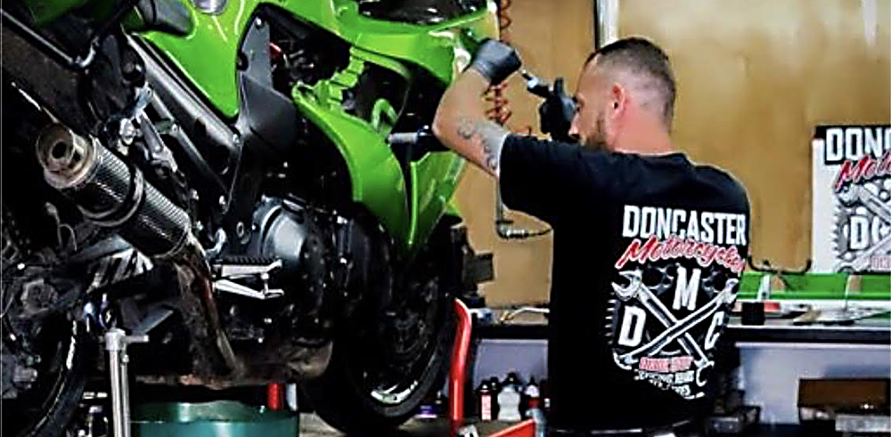 Mechanic topping up and servicing a motorbike - Motorcycle Servicing Doncaster